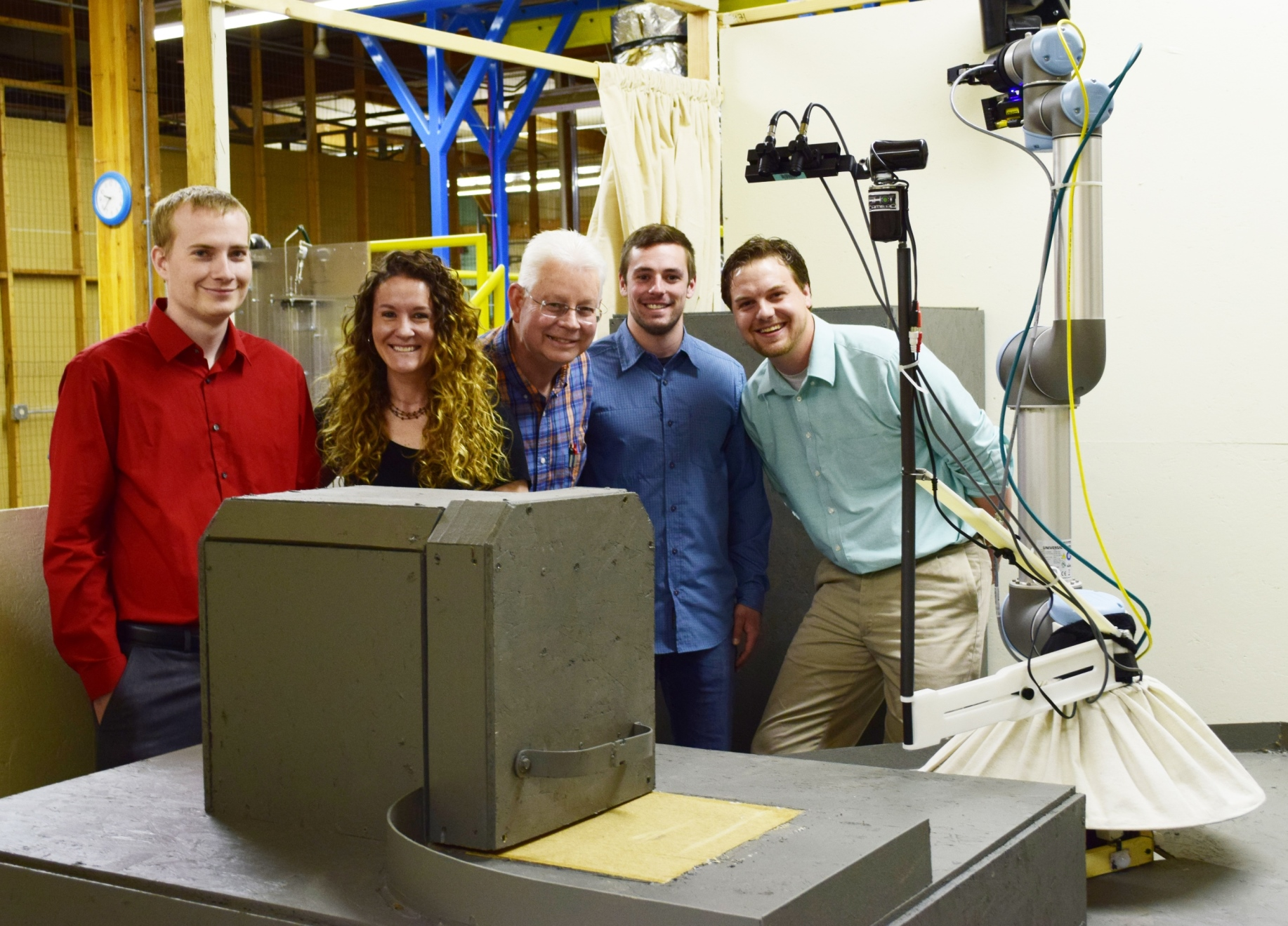 The intern team with their robot (to the right) inside of the mock-up cell. Left to right: Jerron Bennett, Larinda Nichols, mentor Kevin Croft, Sage Thibodeau and Cody Race.