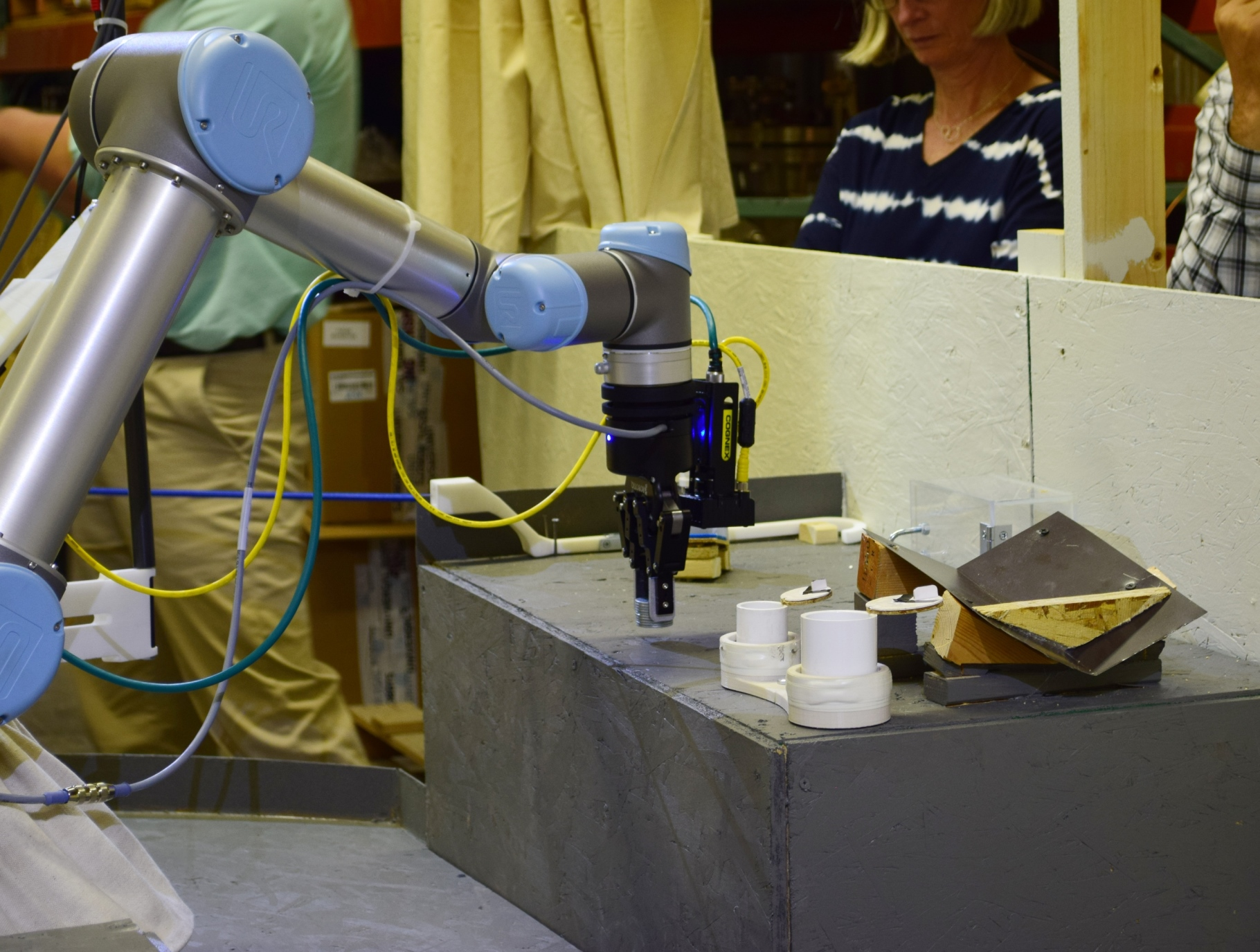 The robot removed the sample from the clear transfer box, out of the two white sample containers, and transported it to the mock-up examination instrument.